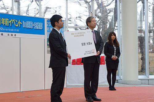 荒川社長から荻野大助様(写真左)へ命名者記念乗車証を贈呈